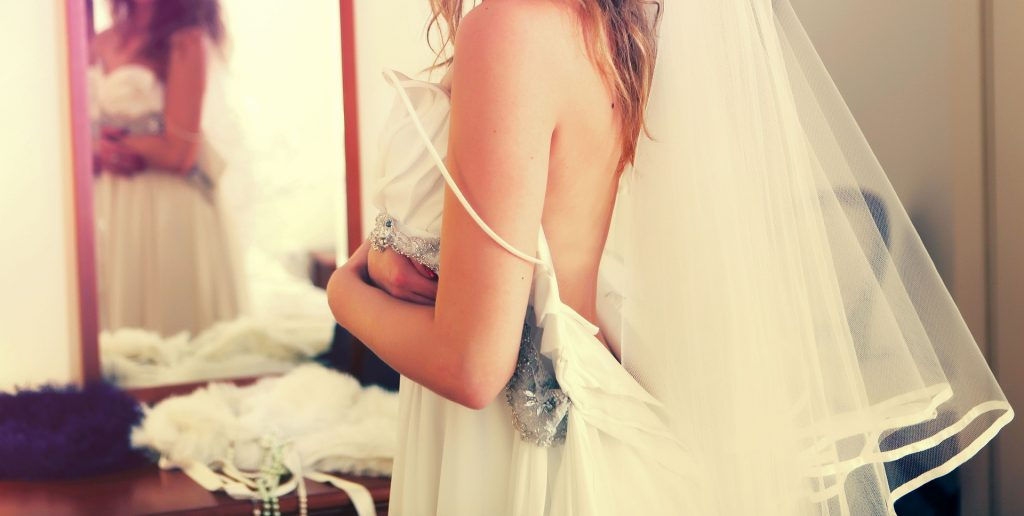 Bride getting dressed - 12 photos you'll regret not taking on your wedding day - The Wedding Club